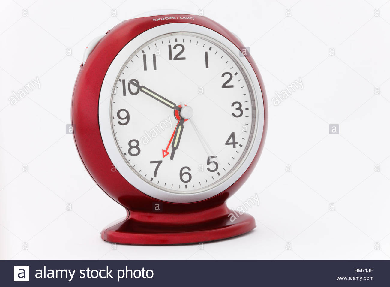 red alarm clock with luminous hands at ten minutes to seven just