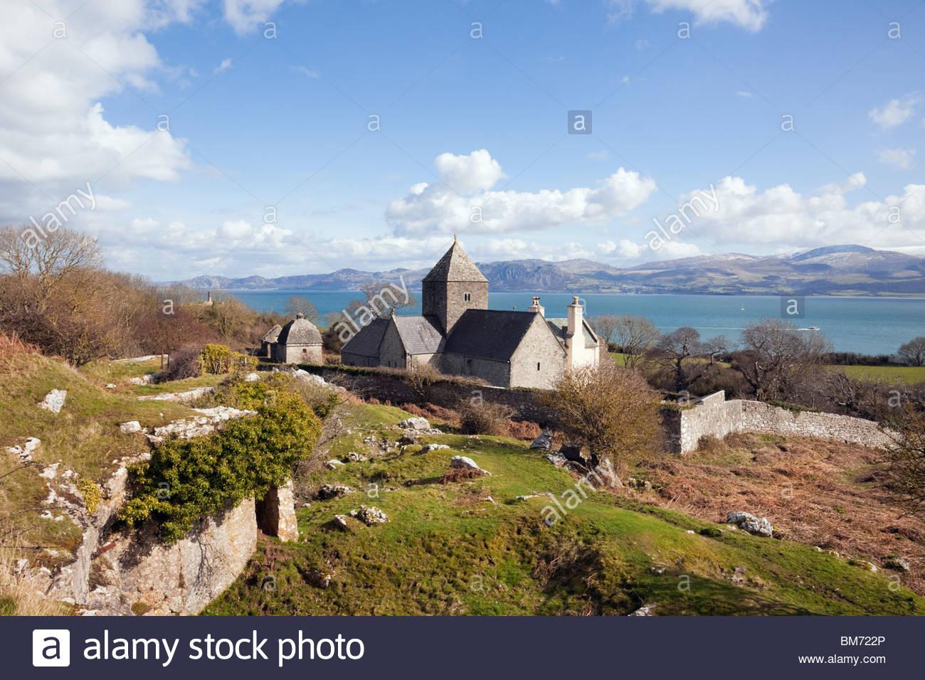 Penmon Priory or St Seiriol's monastery and view to North Wales mainland coast across Menai Strait. Penmon, - Stock Image