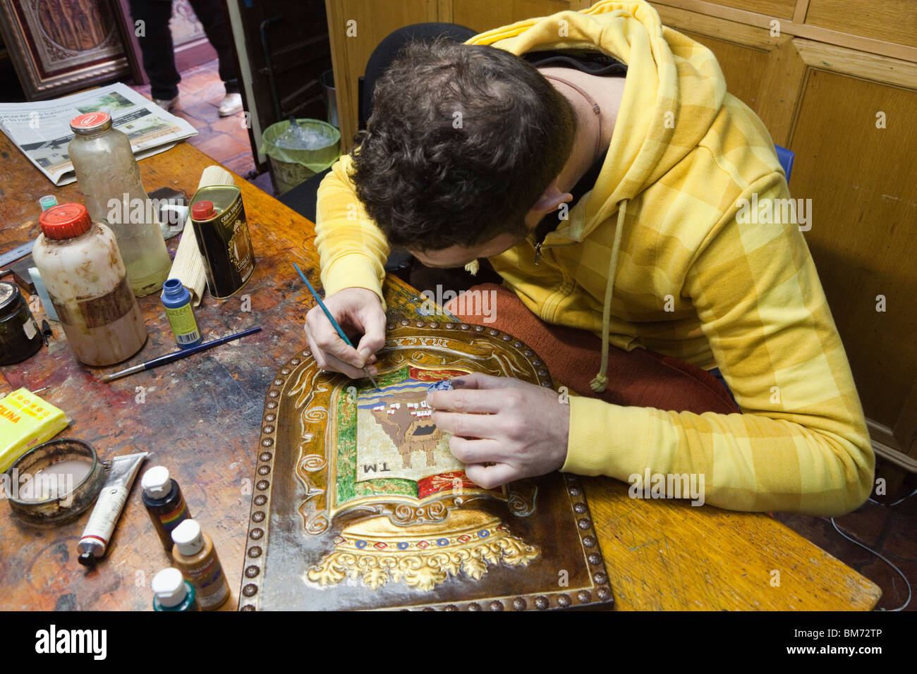 Artisan painting engraved leather in the Taller Meryan, Cordoba, Cordoba Province, Spain. - Stock Image