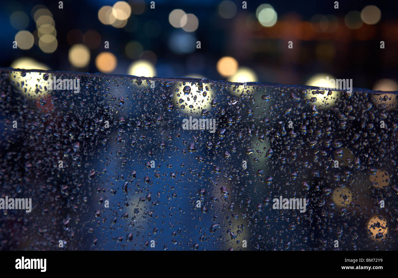 Close up view of raindrops on glass and blurred out lights (from the iconic clocks) behind at London's Canary - Stock Image