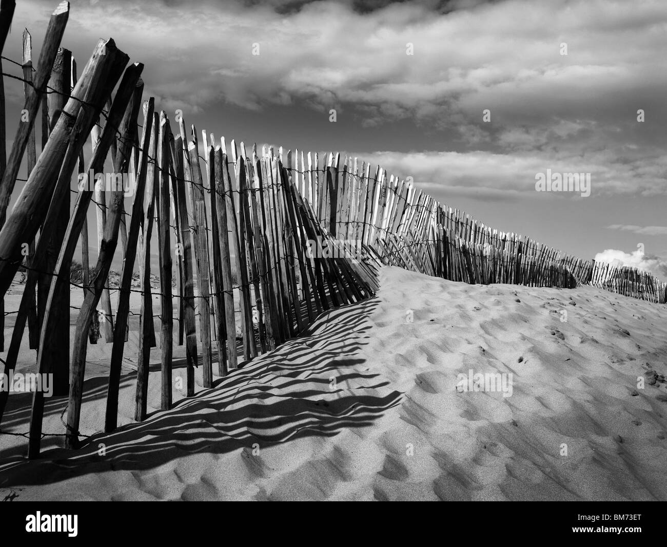 sand dunes at Formby Point Near Liverpool on the Merseyside coast, showing fence, footprints in the sand in black - Stock Image