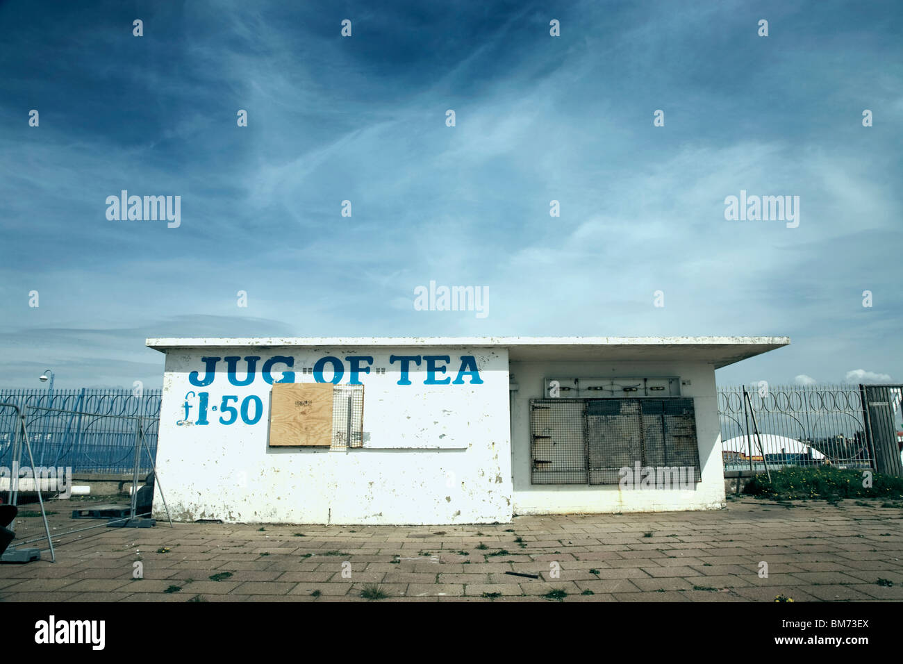 architecture image of a small closed down café building with slogan jug of tea on the front on a sunny day - Stock Image