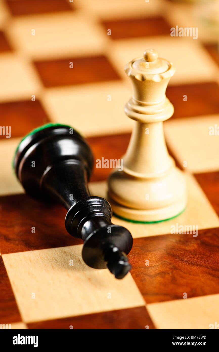 Closeup of checkmate on king by queen winning in chess game - Stock Image