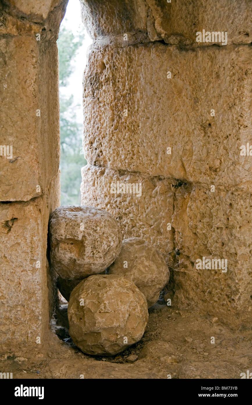 Medieval stone cannonballs in arrow slit window of Ajloun Castle in Jordan Stock Photo