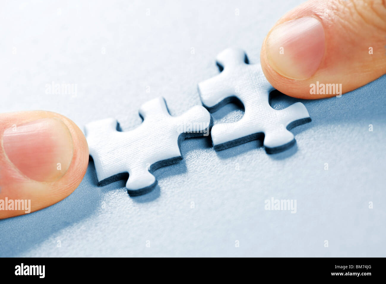 Fingers pushing two matching puzzle pieces together - Stock Image