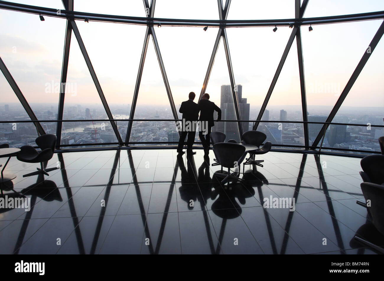Businessmen stand and talk at the top of the Gherkin skyscraper in the city of London, U.K. - Stock Image