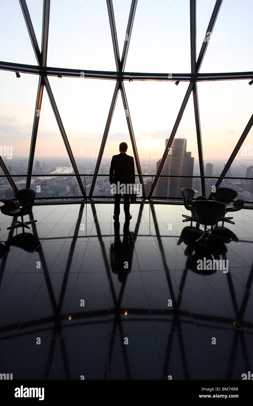 A businessman stand with his briefcase at the top of the Gherkin skyscraper in the city of London, U.K. - Stock Image