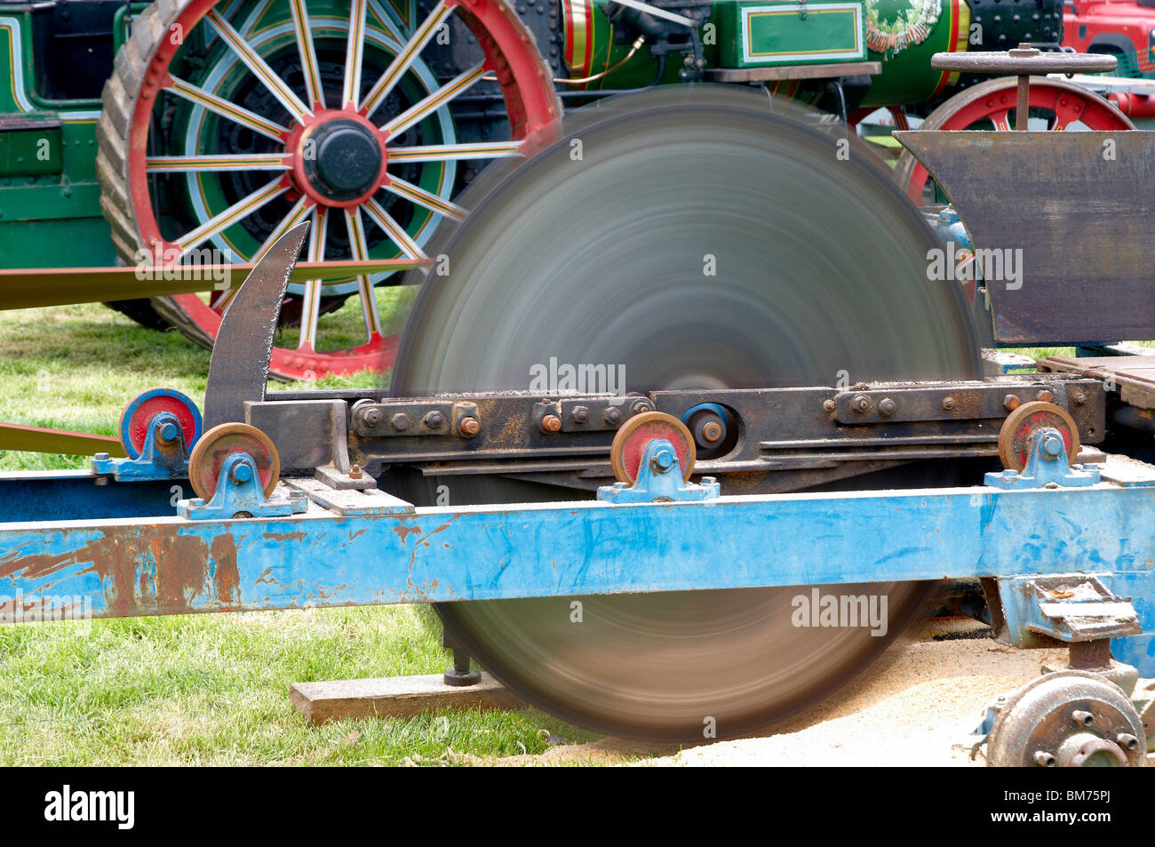 Whirling saw blade on a portable saw bench driven via a belt from a steam traction engine - Stock Image