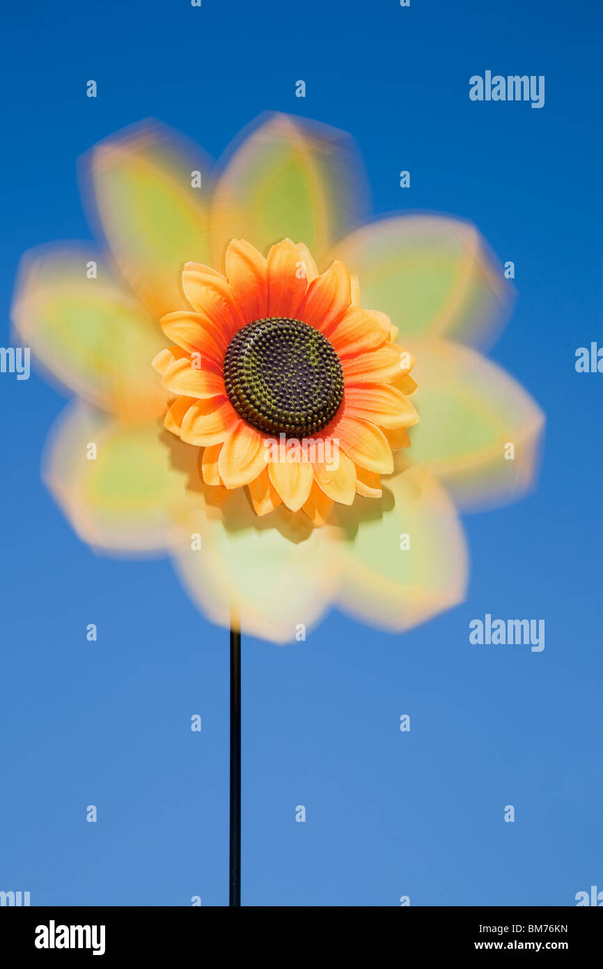 UK, Europe. Artificial Sunflower flower spinner spinning in the wind with blue sky - Stock Image