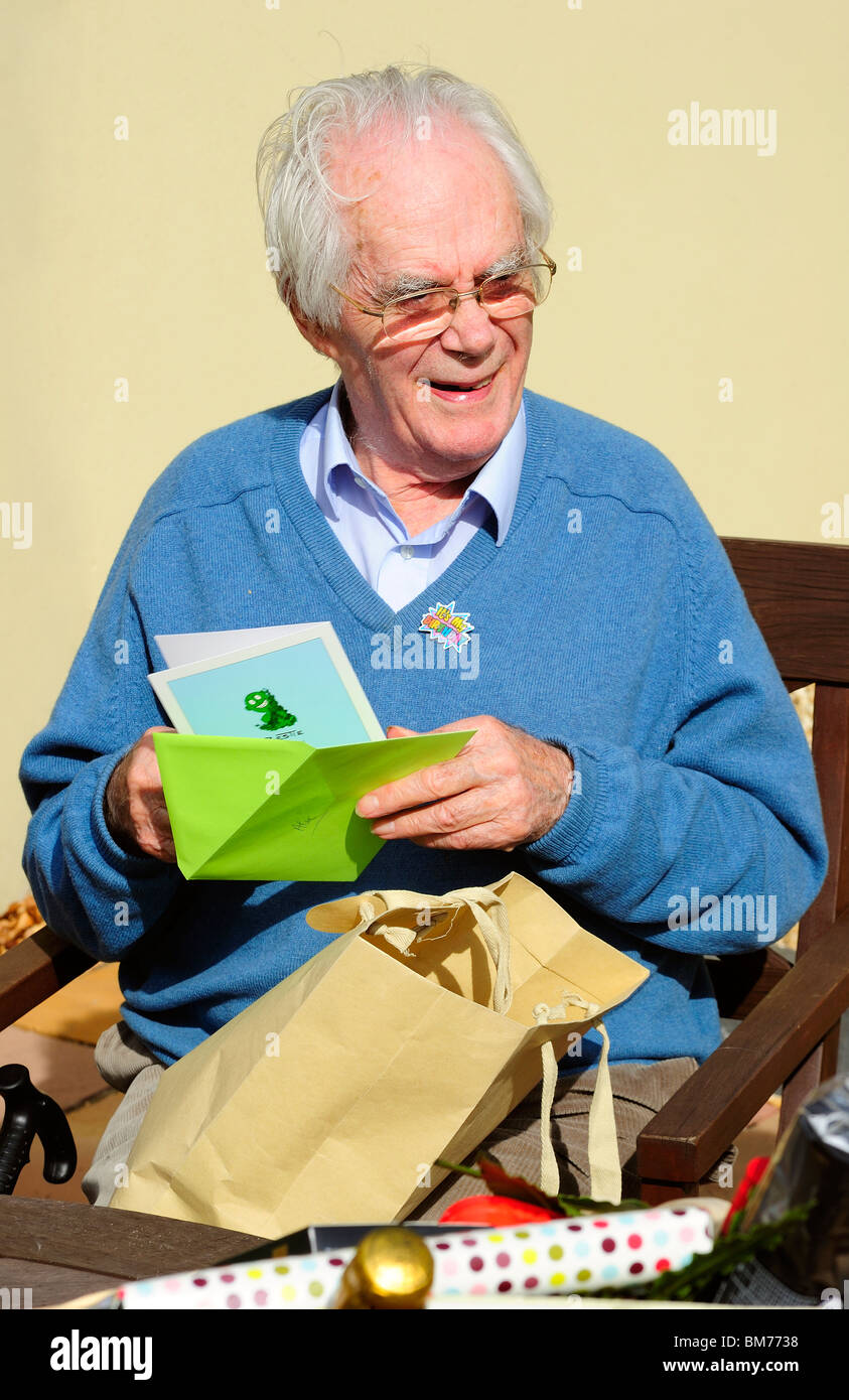 An Older Man Laughs As He Opens A Cartoon Birthday Card On His 90th Badge Is Pinned To Sweater