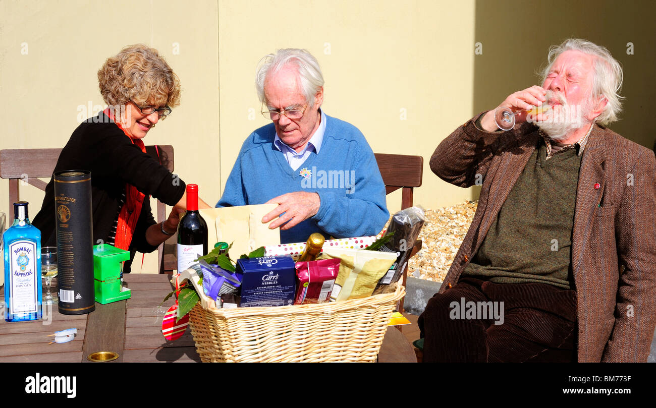 A younger woman helps an older man open presents on his 90th birthday whilst another old man drinks wine. - Stock Image