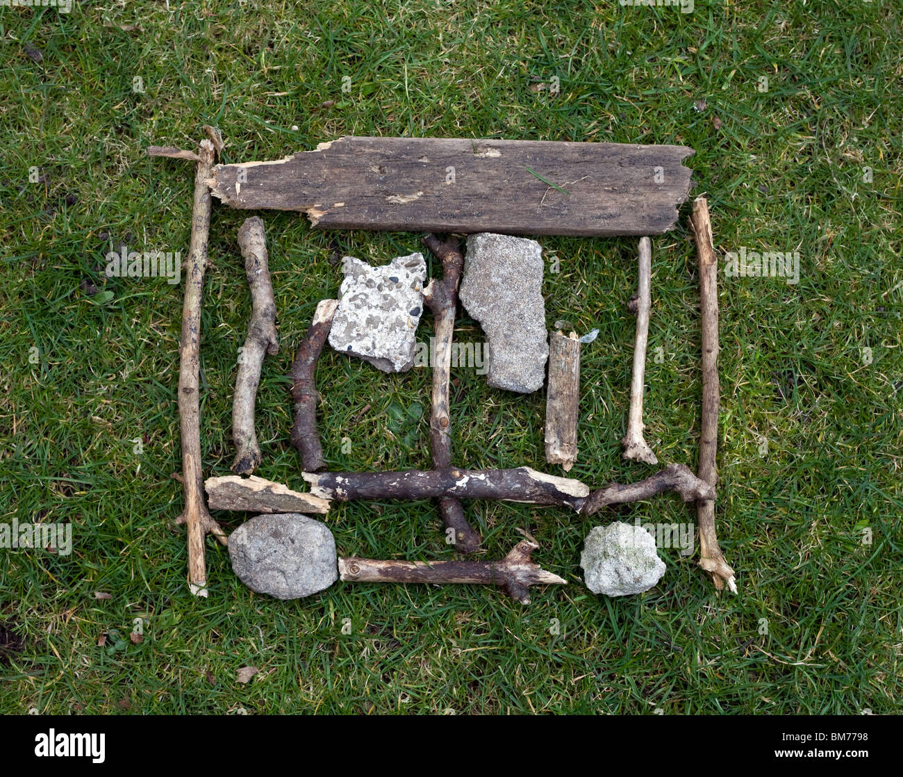 A piece of environmental art, a practical piece of homework made with sticks, stones and grass - Stock Image