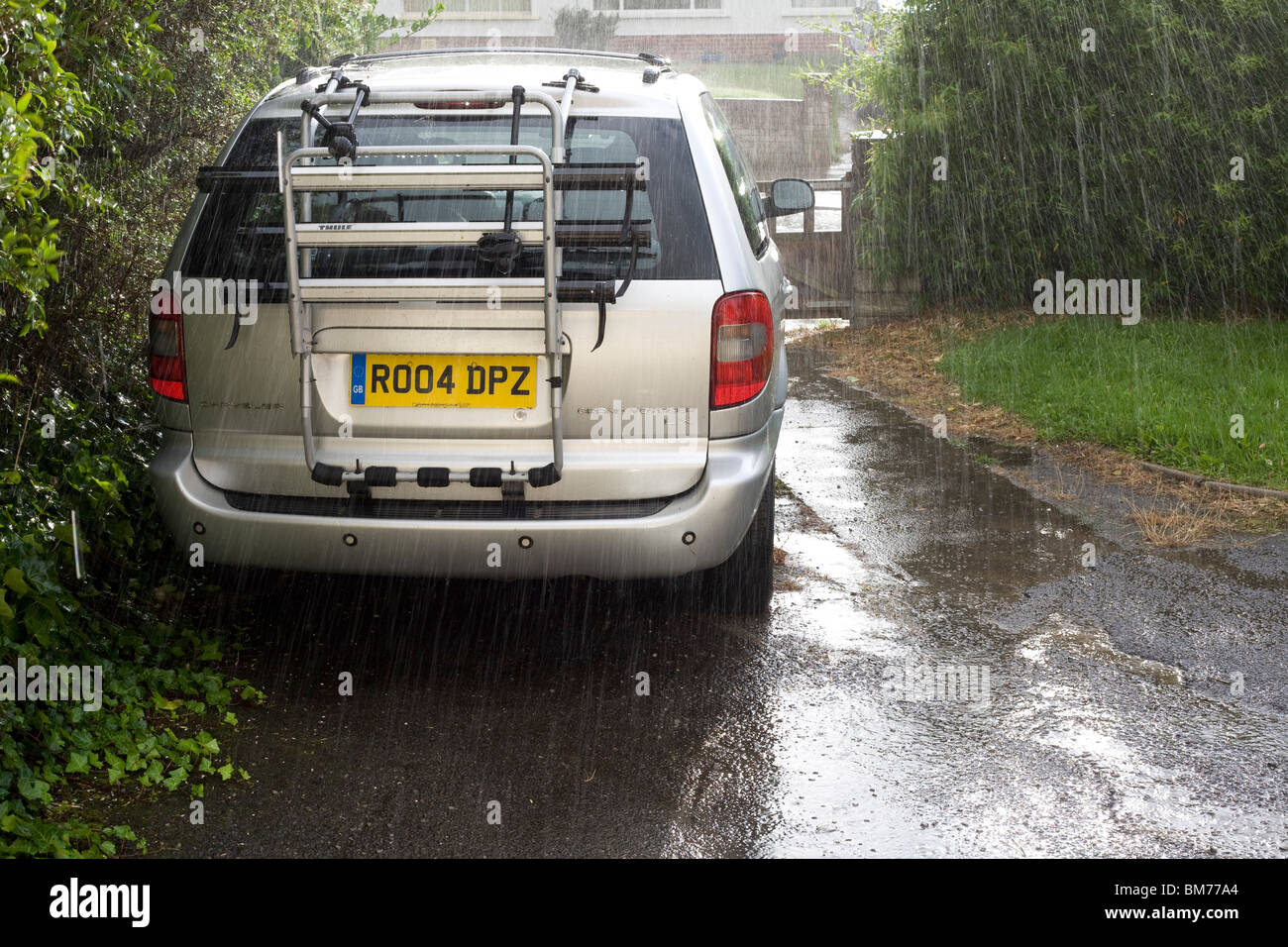 A torrential rain shower falls on a Chrysler Grand voyager sitting on its owners drive - Stock Image