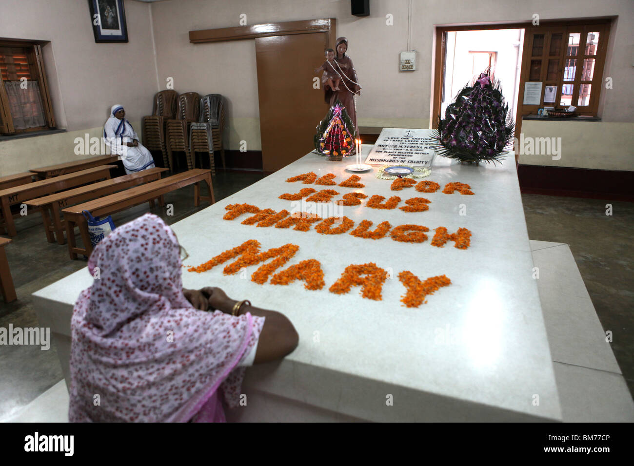 A num prays at the tomb of Mother Teresa at Mother House in Kolkata, formerly called Calcutta in West Bengal, India. Stock Photo