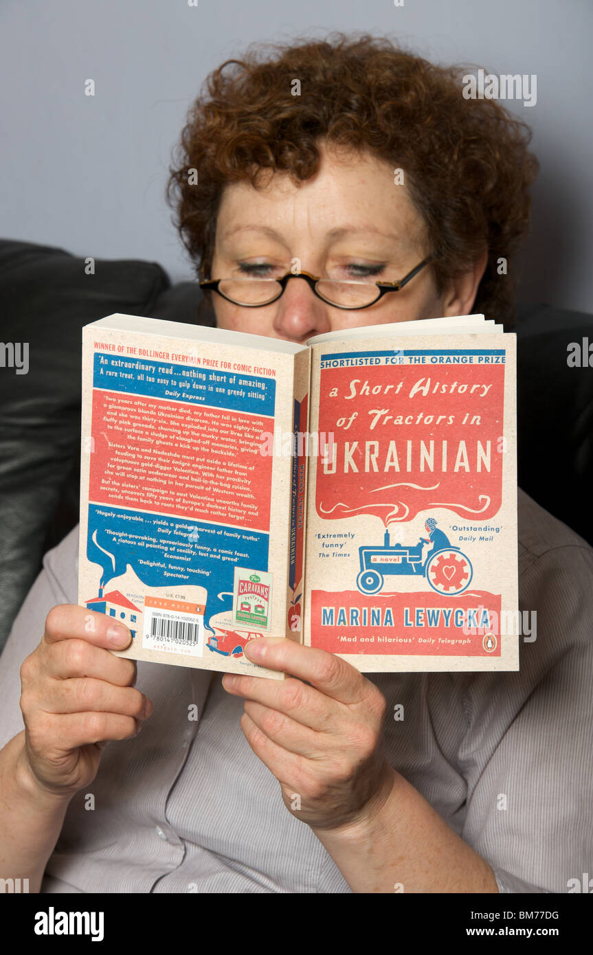 Woman reading a paperback book - Stock Image