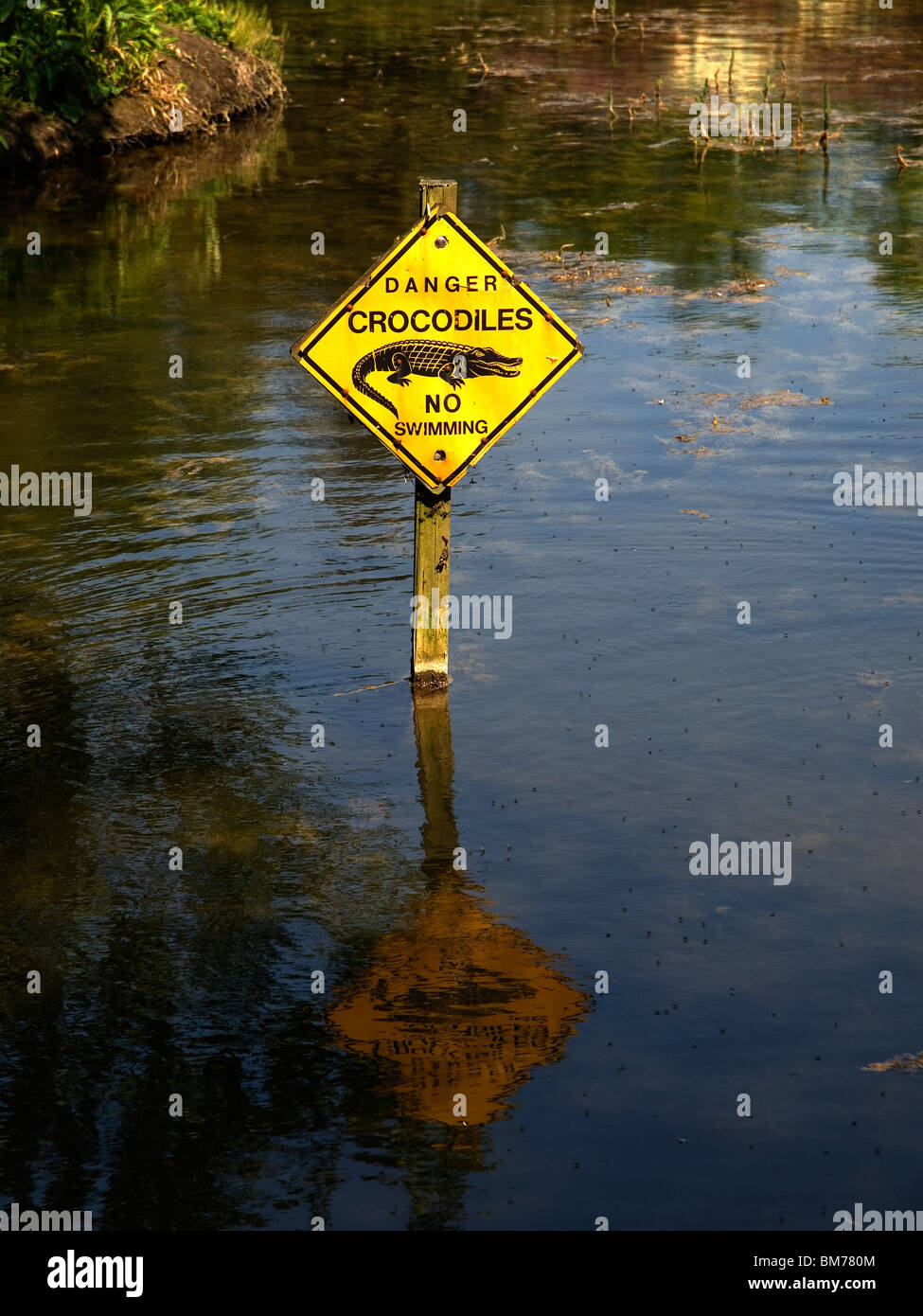 A sign in an English lake saying Danger Crocodiles No Swimming - Stock Image