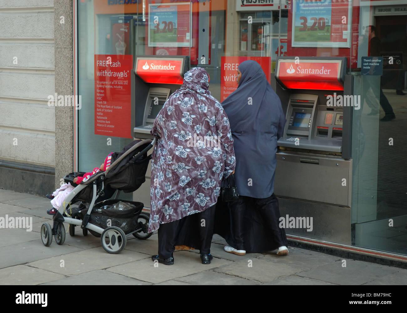 muslim women using bank cashpoint, Northampton, England, UK - Stock Image