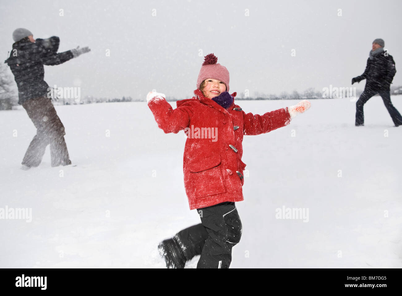 Two parents and their daughters having a snowball fight Stock Photo