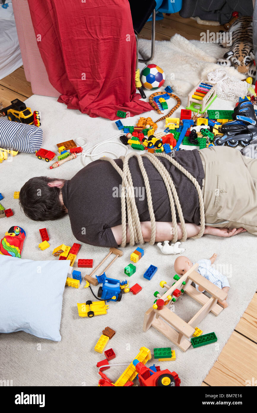 A tied up man in a children's playroom - Stock Image