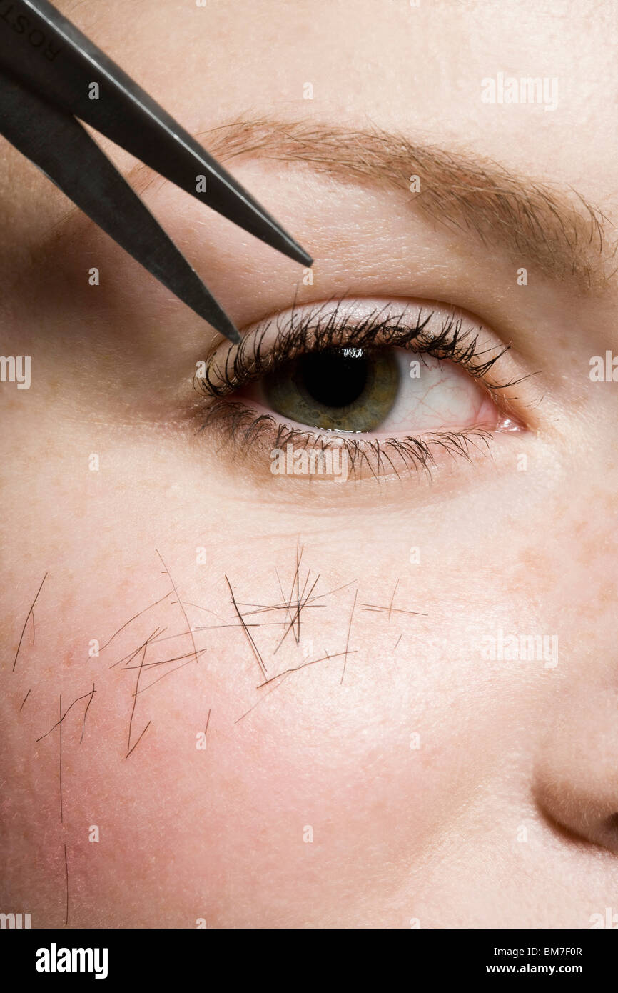 Scissors cutting hair on a woman, detailed shot of eye - Stock Image