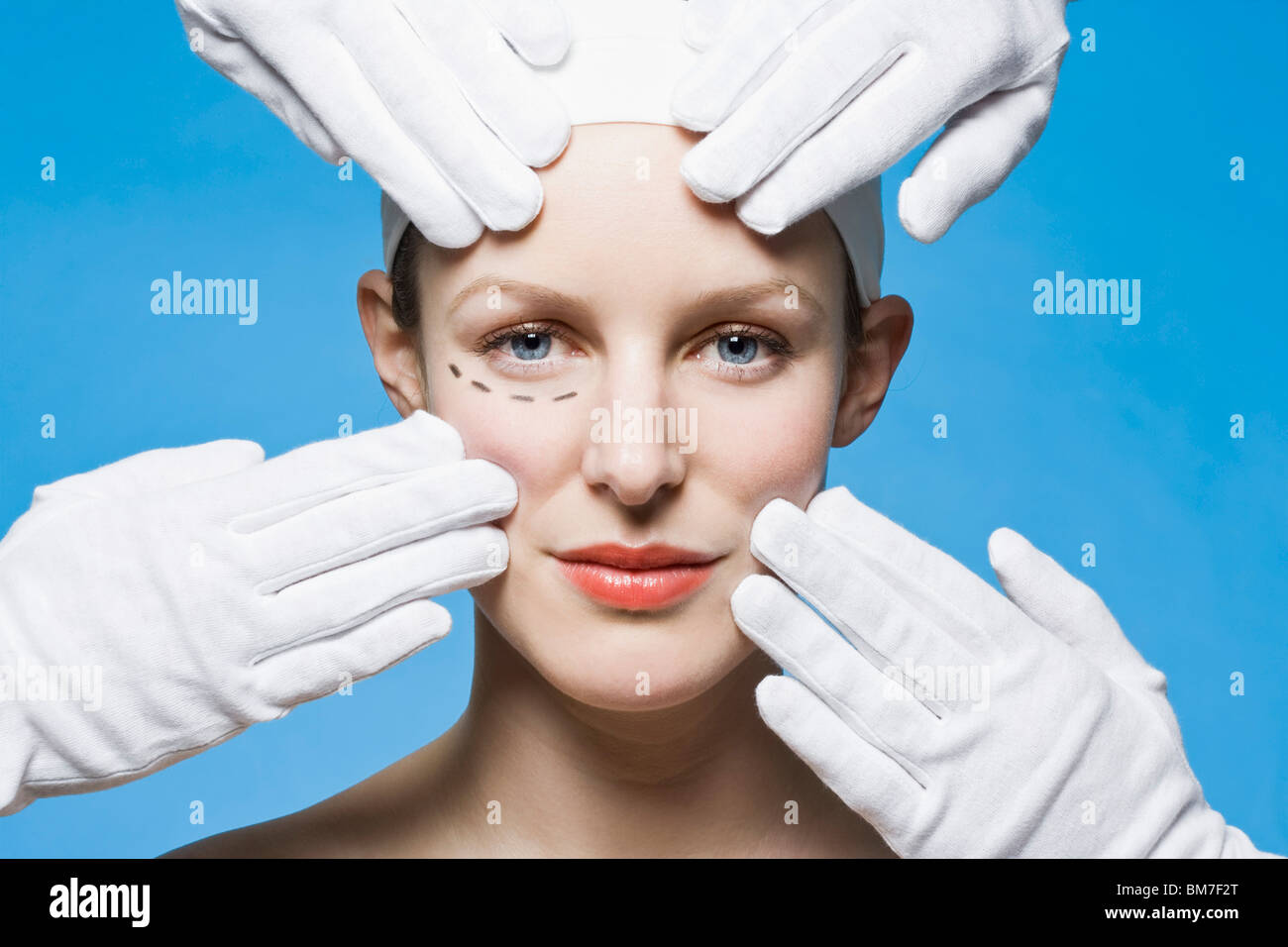 Two healthcare workers, detail of hands, preparing a woman for plastic surgery, headshot - Stock Image