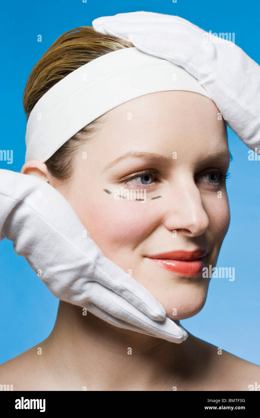 A healthcare worker, detail of hands, preparing a woman for plastic surgery, headshot - Stock Image