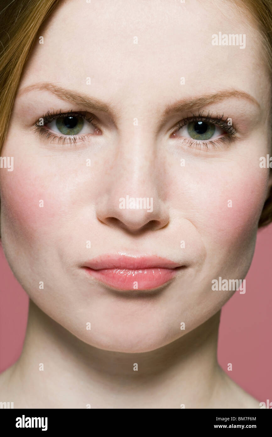 A woman grimacing in irritation, extreme close up - Stock Image