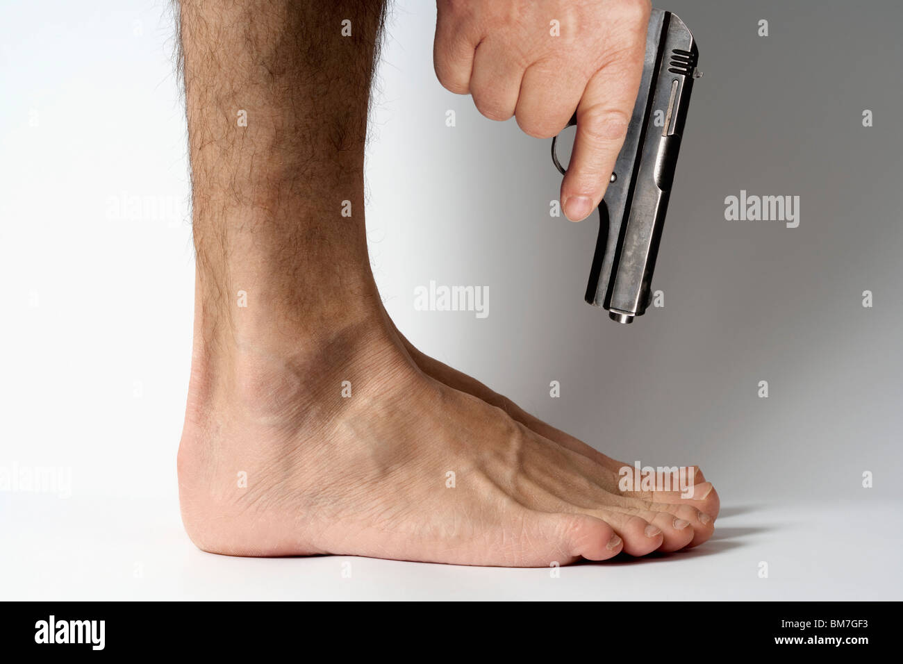 Shoot yourself in the foot - Stock Image