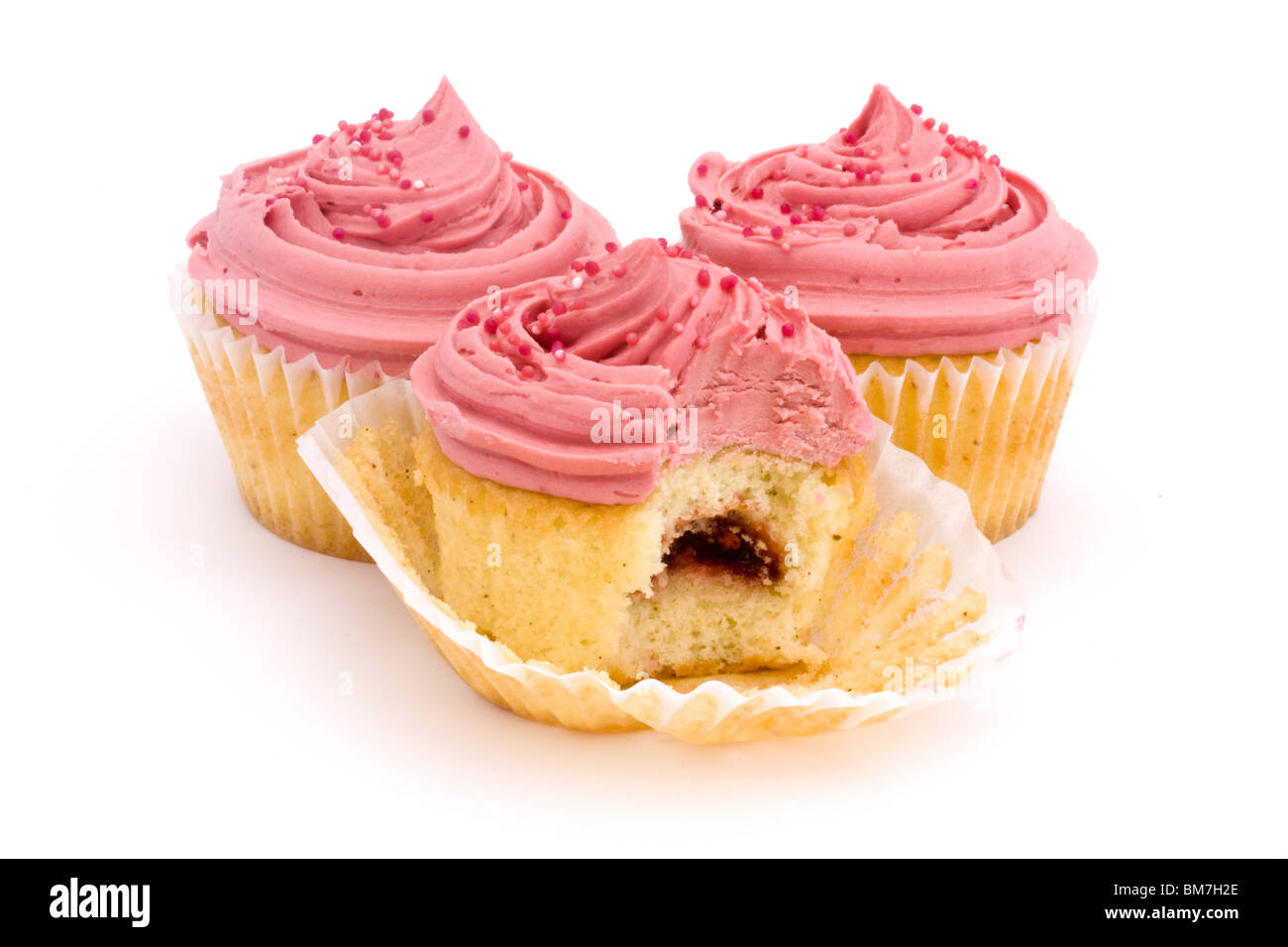 three pink cup cakes on a white background with one bite taken - Stock Image