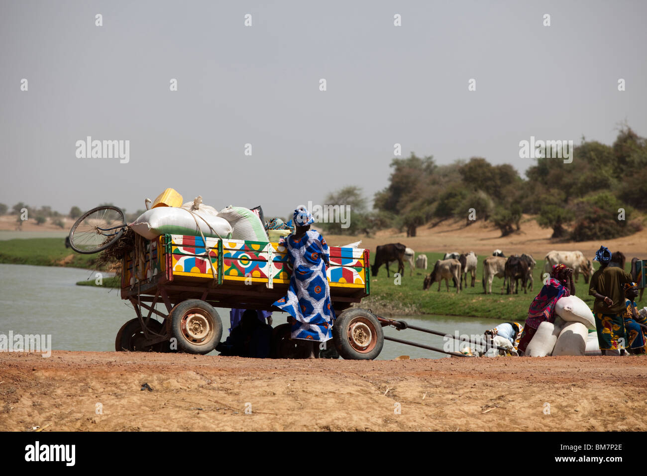 Families in colorfully-painted donkey carts wait for a canoe to take them across the river to the historic town - Stock Image