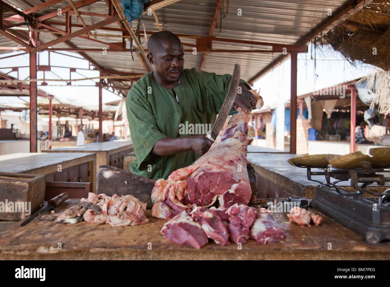 A butcher cuts meat in the market in Segou, Mali. - Stock Image