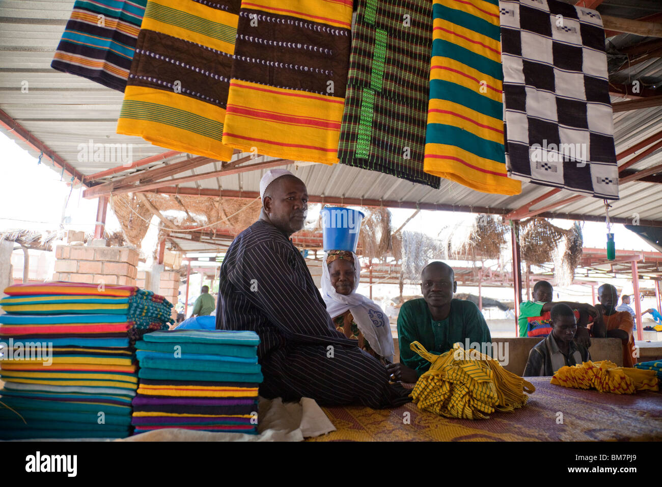 A Fulani man sells strips of cloth woven together into colorfully-patterned breakfasts in the market in Segou, Mali. - Stock Image