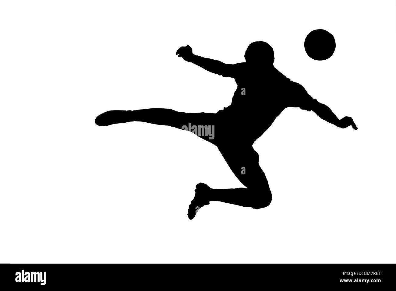 A silhouette of a soccer player shooting a ball - Stock Image