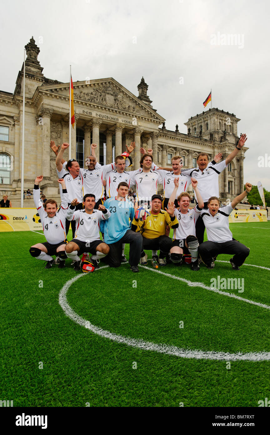 A cheering German blind football international team  in front of the Reichstag building, Berlin, Germany, Europe - Stock Image
