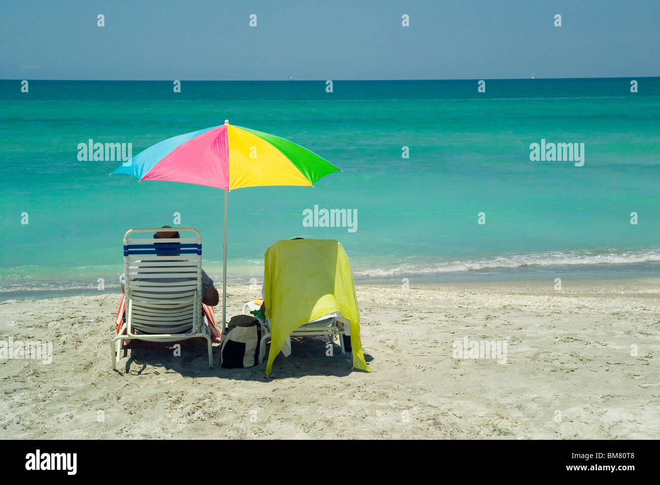 Vacationers enjoy relaxing with a peaceful view of the pristine Gulf of Mexico turquoise waters along the Longboat - Stock Image