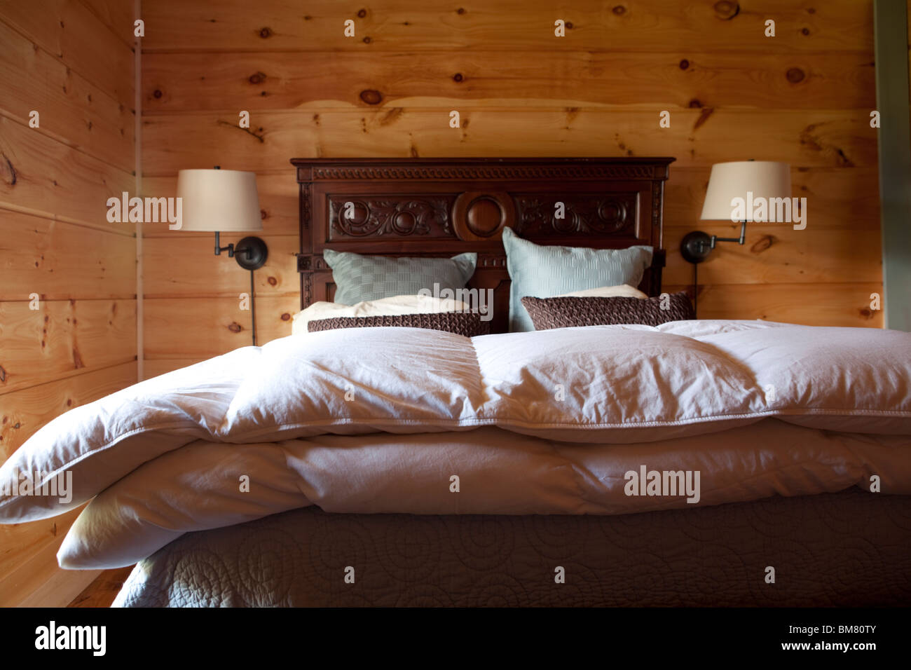 Wooden cottage bedroom with bed duvet double bed and pillows. American countryside. USA - Stock Image