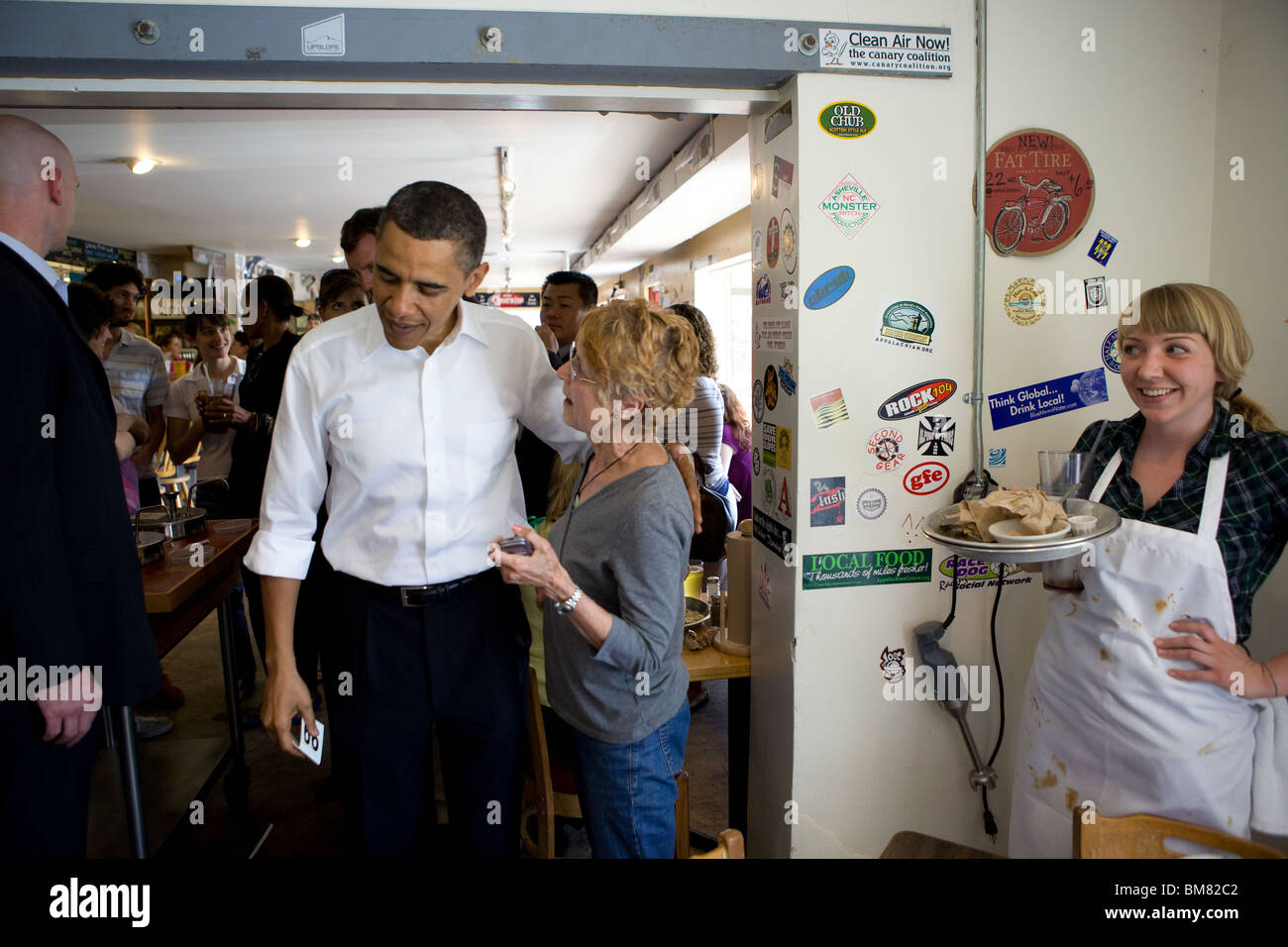 President Barack Obama and First Lady Michelle Obama talk with patrons at 12 Bones restaurant in Asheville, N.C., - Stock Image