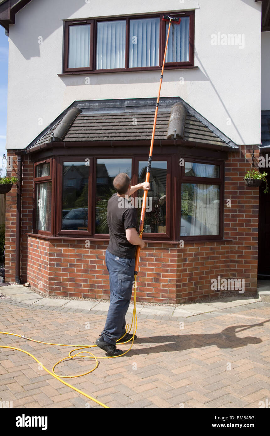 North Wales UK Self employed windown cleaner man using a pure water fed pole window cleaning system with no need Stock Photo