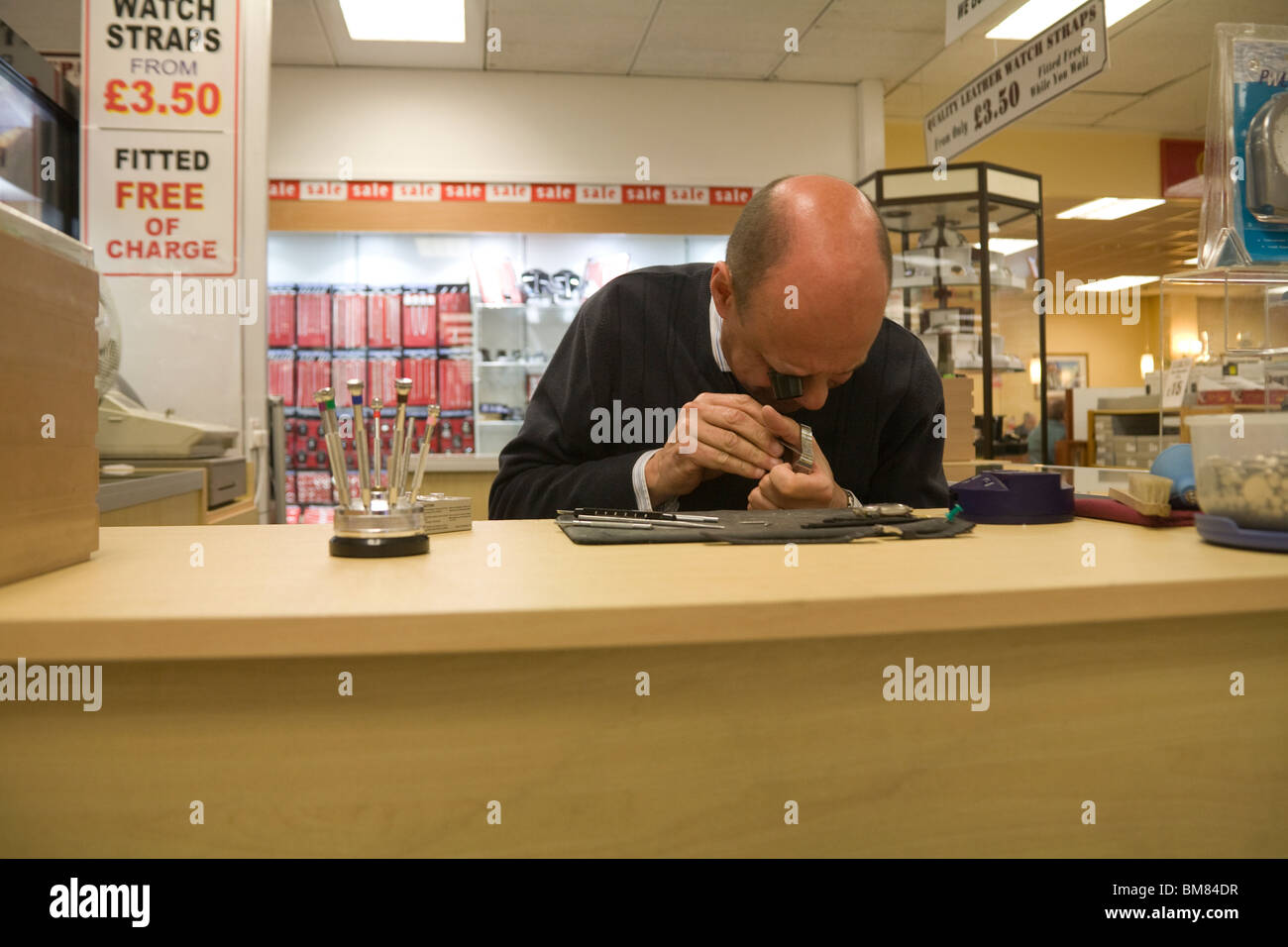 Close up of a jeweller changing a watch battery in a Department Store - Stock Image