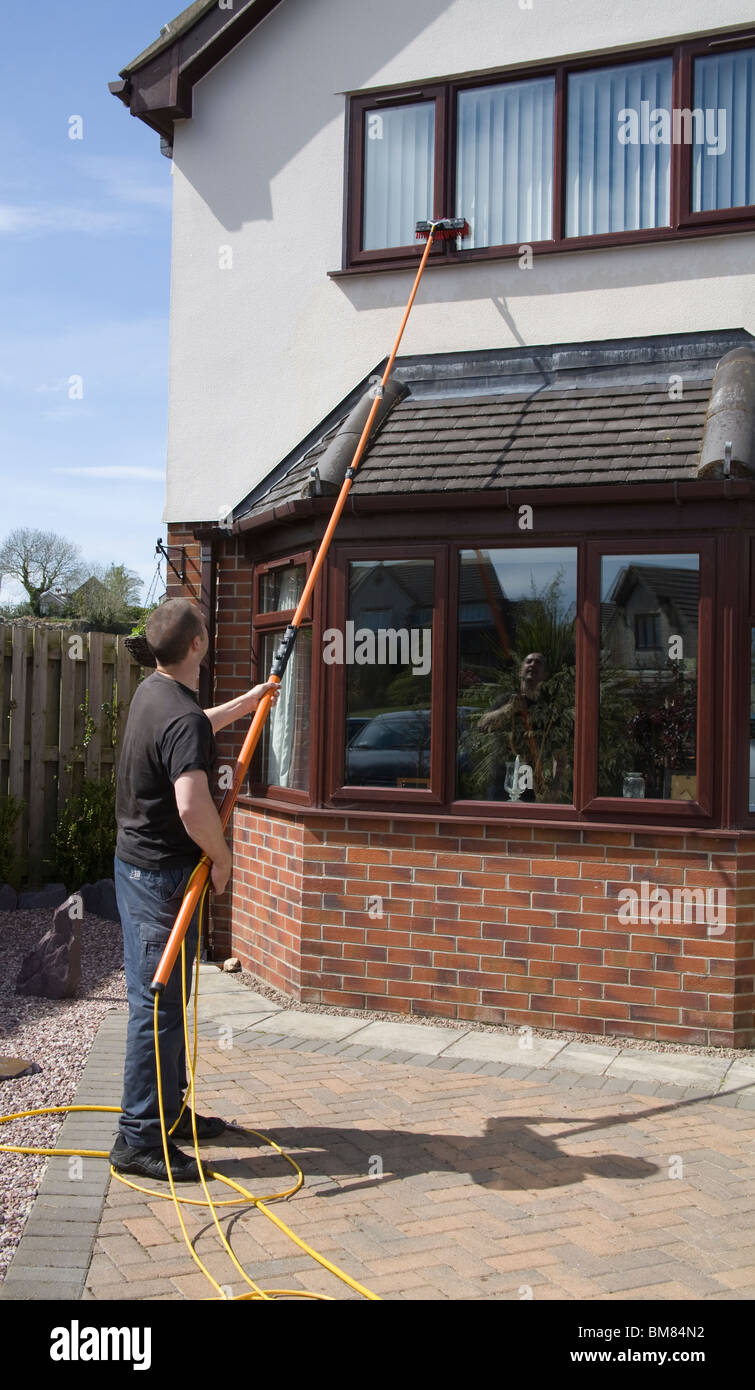 North Wales UK Self employed window cleaner man using a pure water fed pole window cleaning system with no need Stock Photo