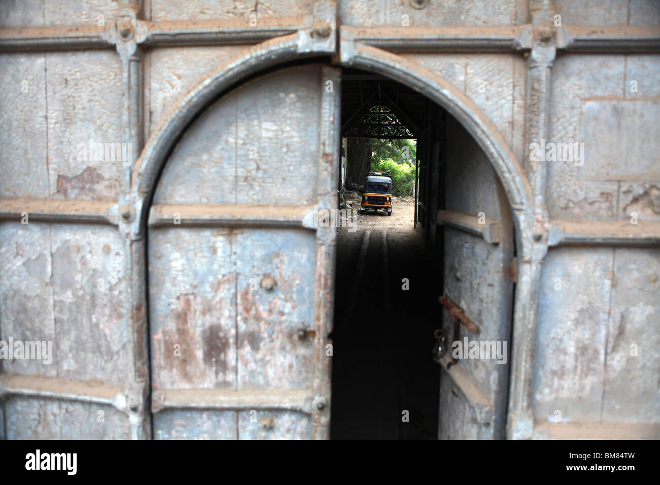 View through an open doorway, showing a tuk tuk in the distance in Jew Town in Kochi, formerly known as Cochin in - Stock Image