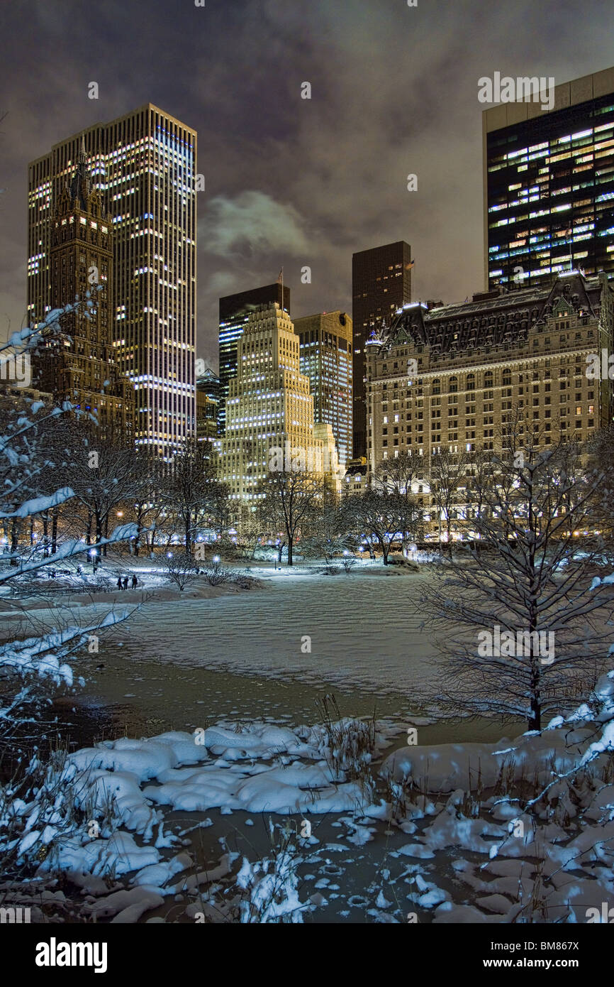 Manhattan skyline including the Plaza Hotel & GM Building at night as seen from Gapstow Bridge in Central Park after Stock Photo