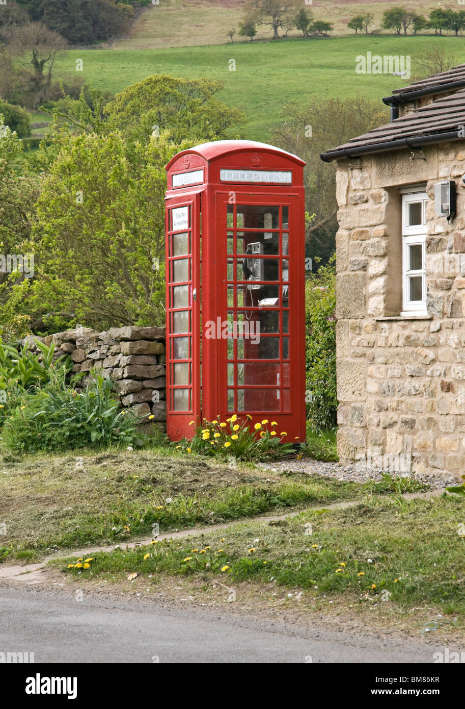 Red telephone box outside the village hall in the village of East Witton, Wensleydale, Yorkshire dales,  North Yorkshire - Stock Image