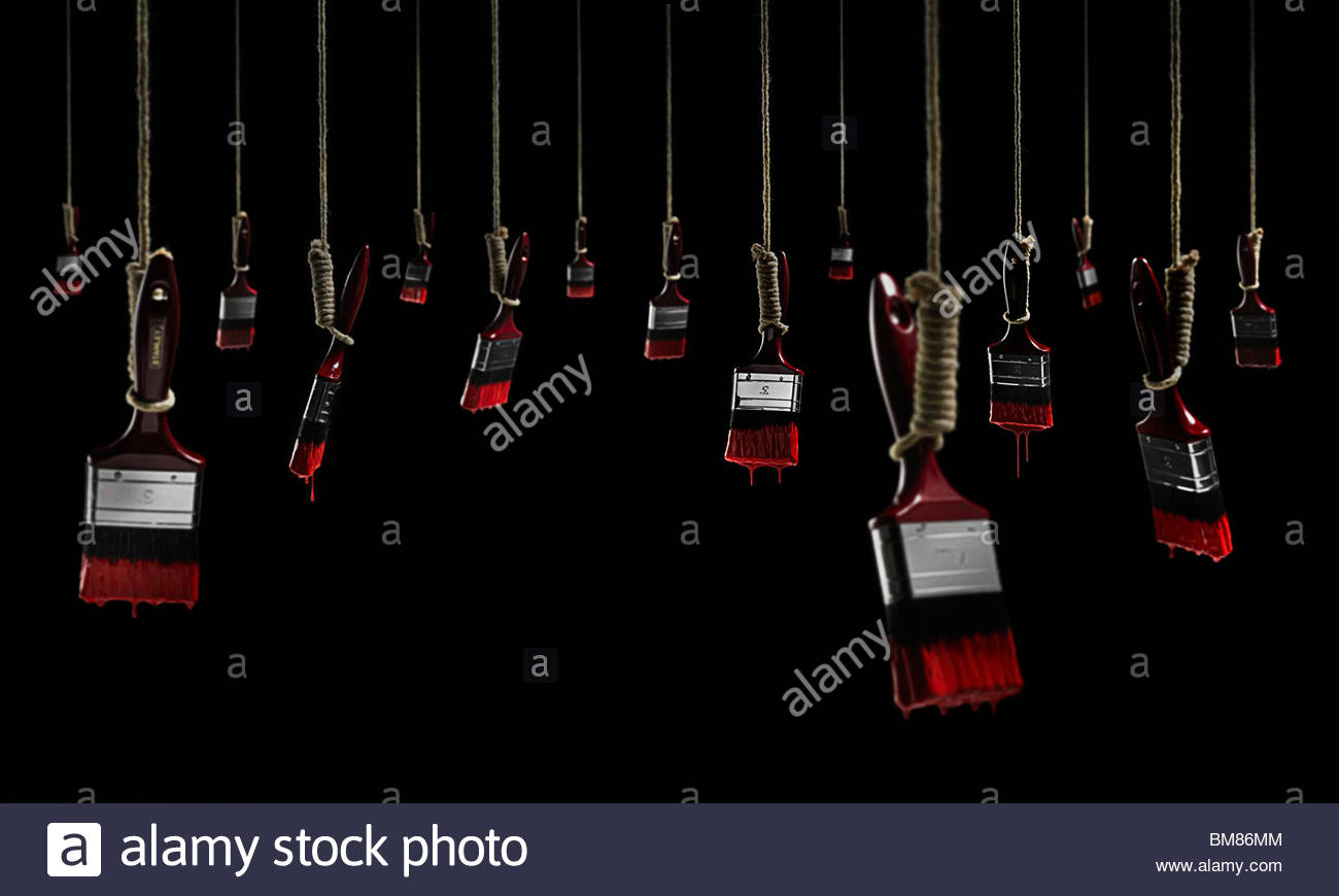 Hanging paint brushes dripping with red paint on a black background - Stock Image