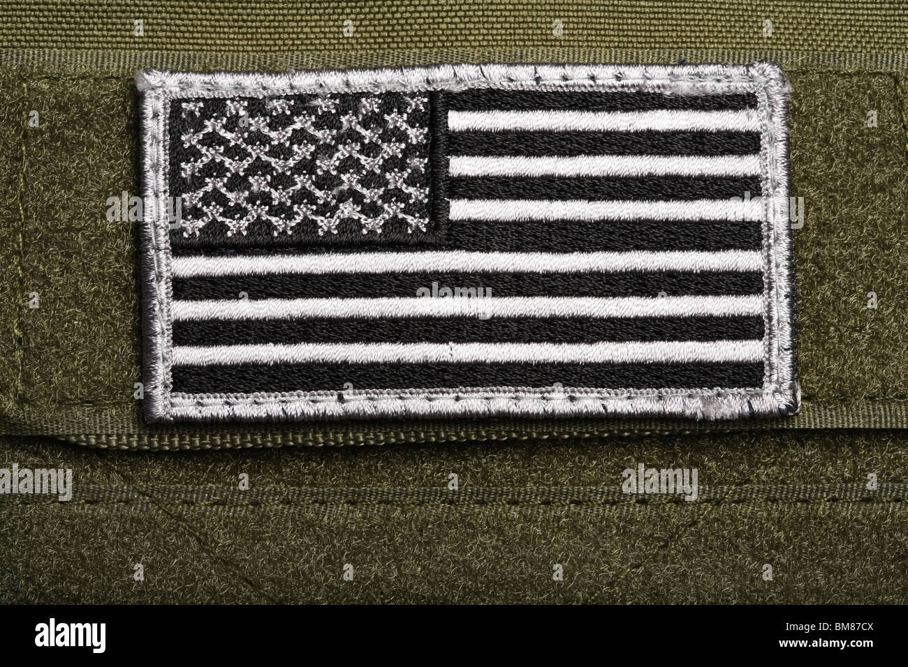American military flag patch on a velcro, green background. Close-up shot. - Stock Image
