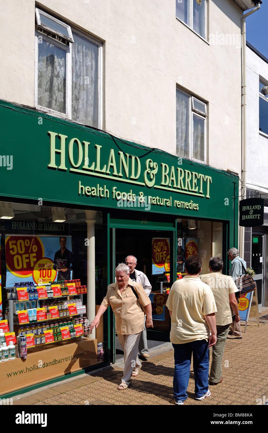 people walking past a Holland and Barrett health food shop in brixham, devon, uk - Stock Image