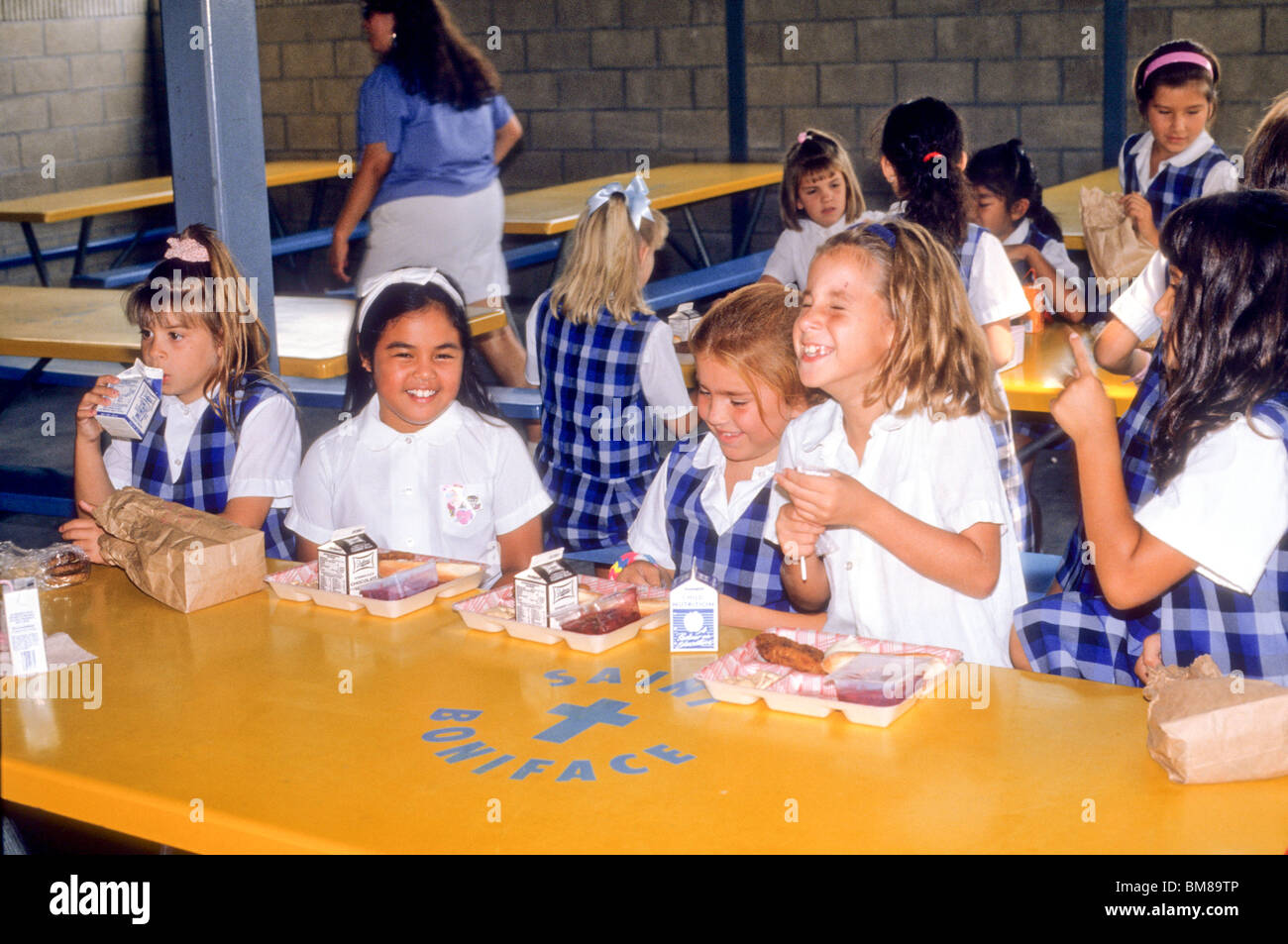 racial mix group of school girls eat lunch at table laugh share fun happy white Hispanic Asian - Stock Image