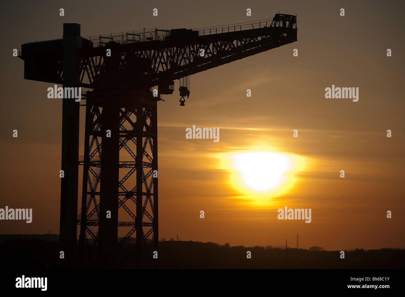 The Titan crane in Clydebank on the outskirts of Glasgow is silhouetted against the sunset. - Stock Image