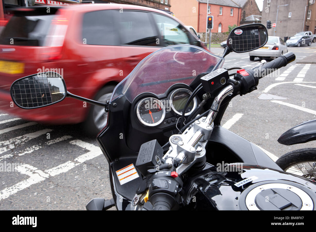 In town motorcycle handlebars looking down at speedo and instruments dials with car speeding past in background - Stock Image