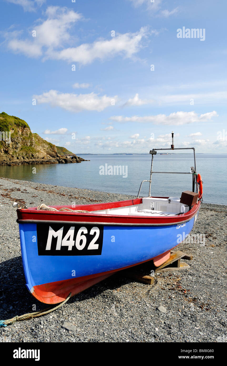 a small fishing boat moored on the shingle beach at porthallow in cornwall, uk - Stock Image